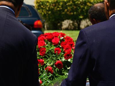 Bei einer Bestattung wird ein großer Roßenstrauß an das Grab getragen.