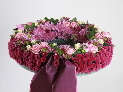 Ein Blumenkranz soll bei einer Bestattung auf das Grab gelegt werden.