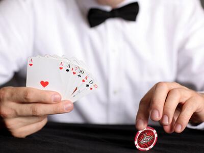 Ein Mitarbeiter eines Casinos hält Karten in der Hand.