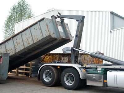 Ein Container wird auf einen Lastwagen geladen.