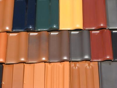 Der Dachdecker verwendet Ziegeln in verschiedenen Farben und Größen.
