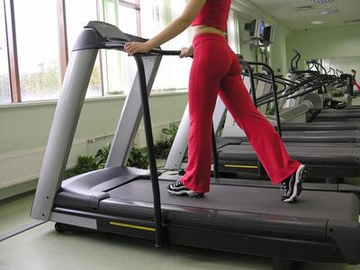 Eine Frau trainiert im Fitnessstudio auf einem Laufband.
