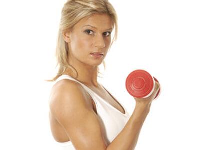 Eine junge Frau trainiert mit einer Hantel im Fitnesscenter.