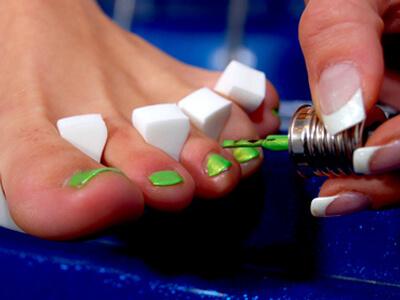 Bei der kosmetischen Fußpflege werden Zehnägel lackiert.