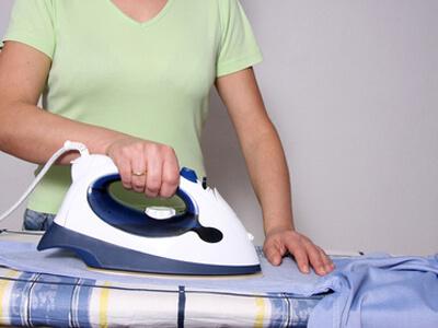 Eine Haushaltshilfe bügelt ein Hemd.