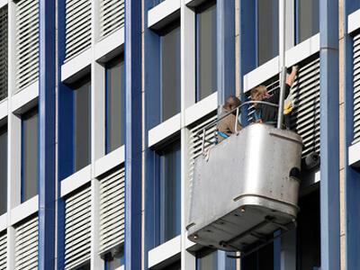 Ein Hausmeisterservice setzt Mitarbeiter zum Fenster putzen ein.