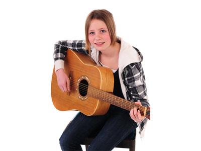 Eine junge Frau lernt das Spielen einer Gitarre im Musikunterricht.