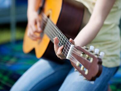 In der Musikschule werden neue Gitarrengriffe gelernt.