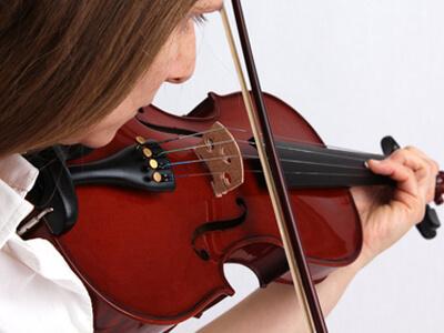 Eine Frau lernt in der Musikschule das Musizieren mit einer Violine.
