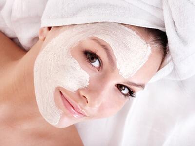 Im Kosmetikstudio bekommt eine junge Frau eine Gesichtsmaske.