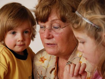 Eine Tagesmutter schaut mit zwei Kindern ein Buch an.
